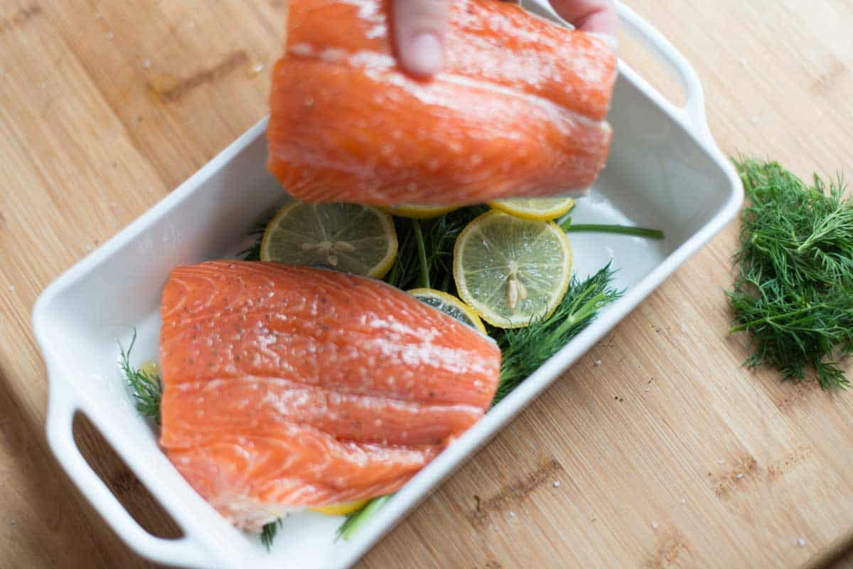 How to Cook Salmon -- For the most tender salmon, bake it on top of lemon slices, herbs, and add a little liquid (like wine, water, or broth).