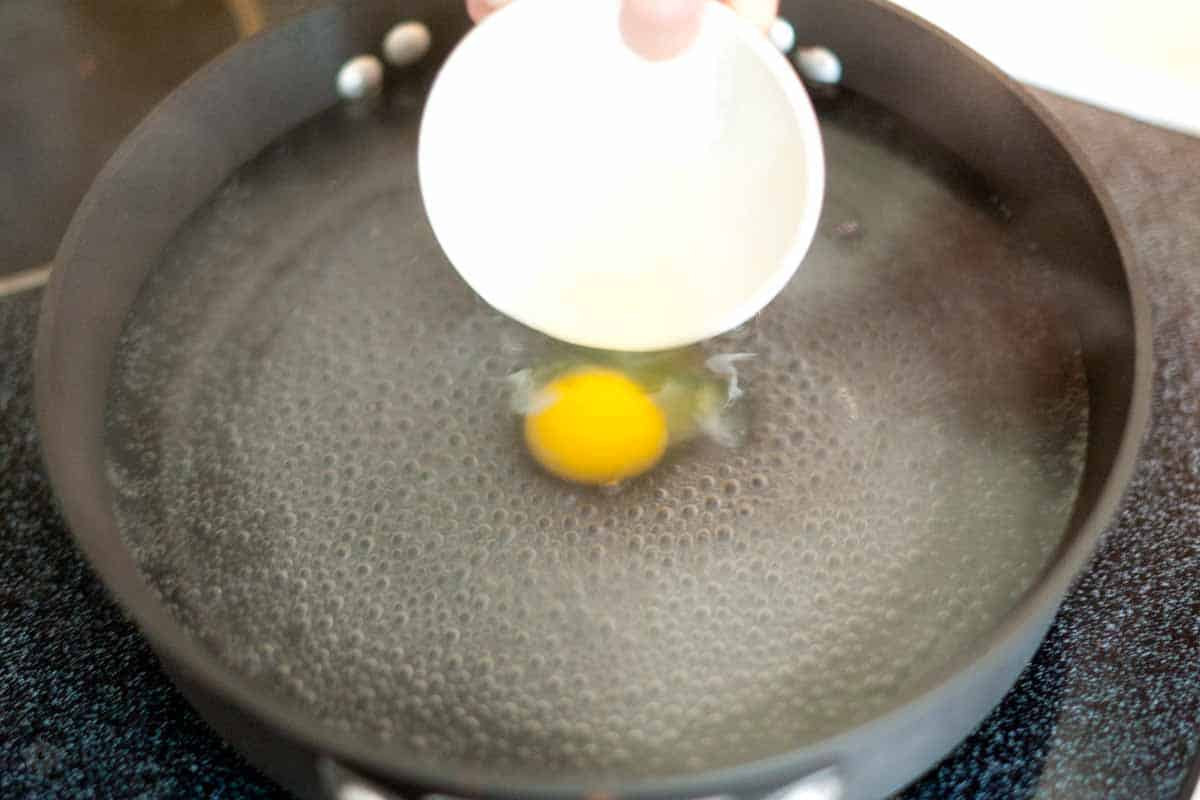 Step 2: Crack egg into a small bowl then add to water