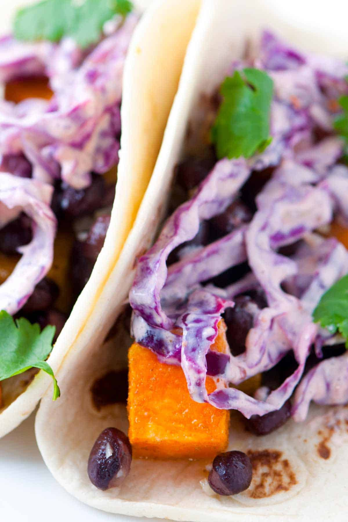Roasted sweet potato and black bean tacos topped with a quick and easy chipotle slaw. Fast and healthy!