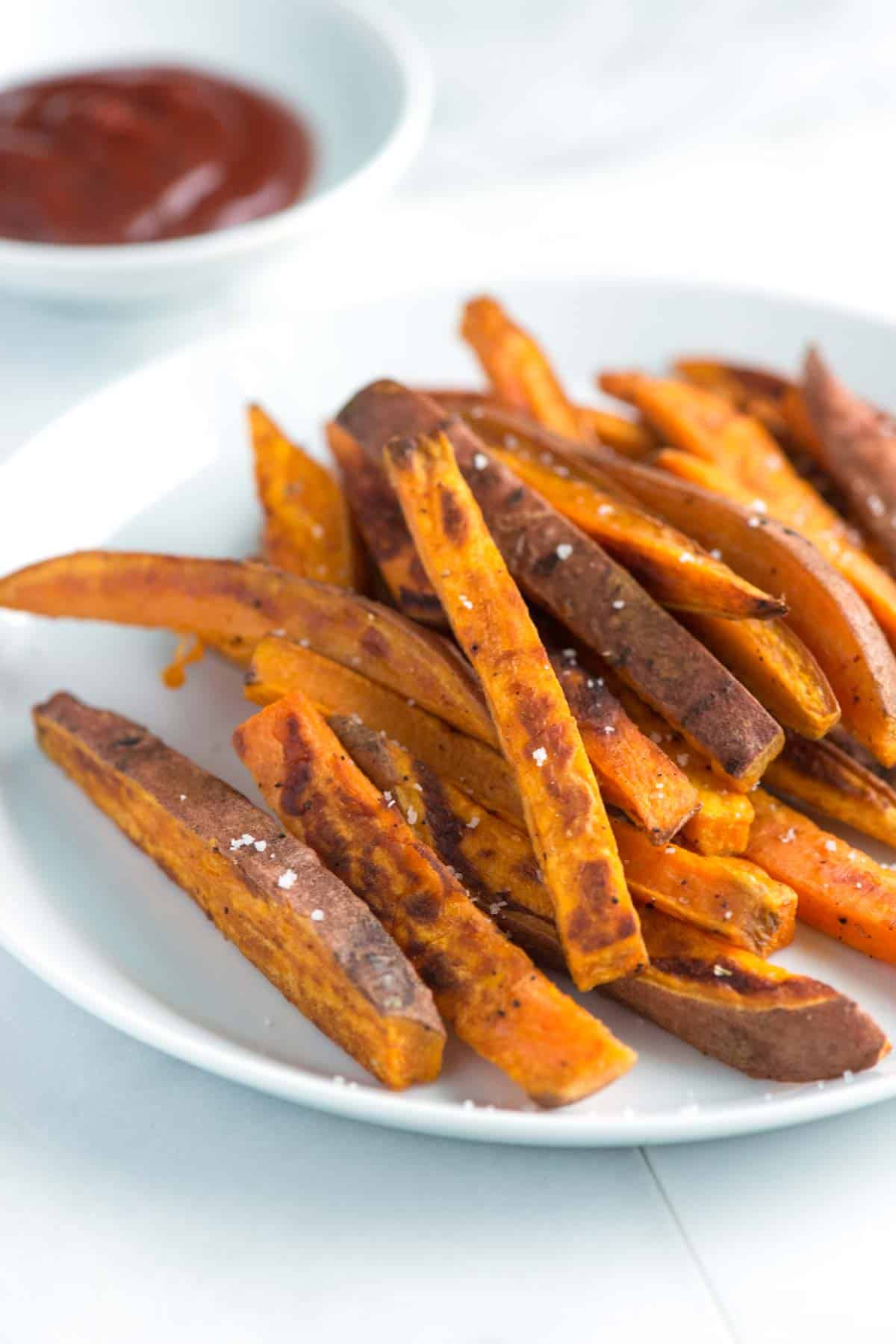 How to make crispy baked sweet potato fries that are caramelized and on the outside and tender on the inside. No fryer needed here. Consider making a double batch, these are addictive.