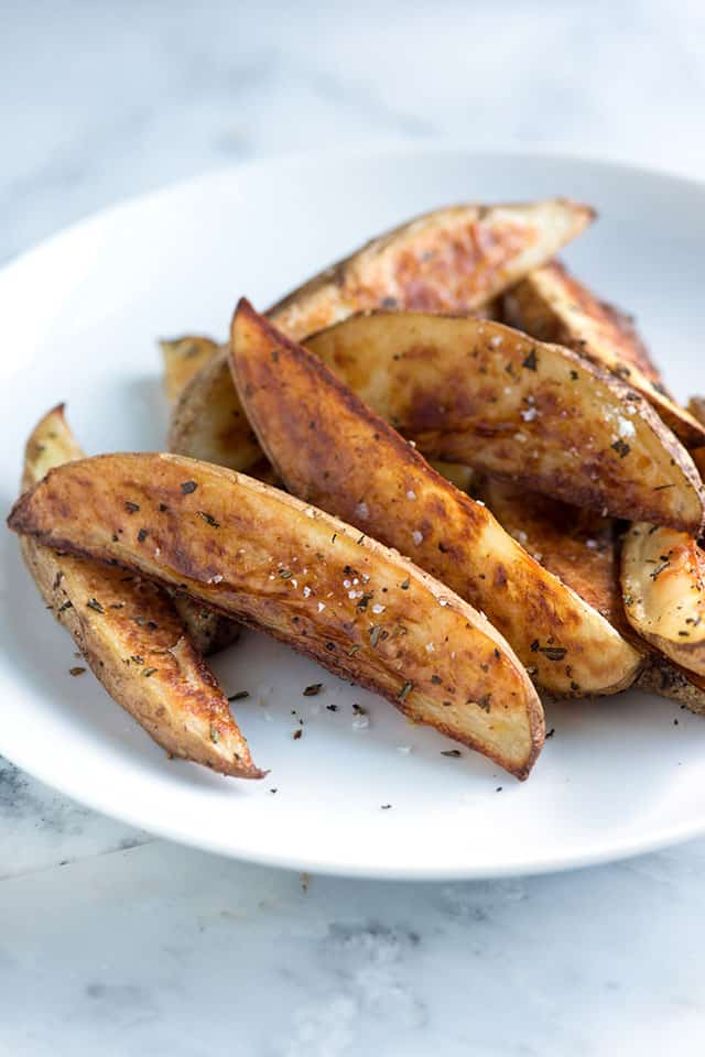 Roasted potato wedges recipe with olive oil, salt, pepper and rosemary.