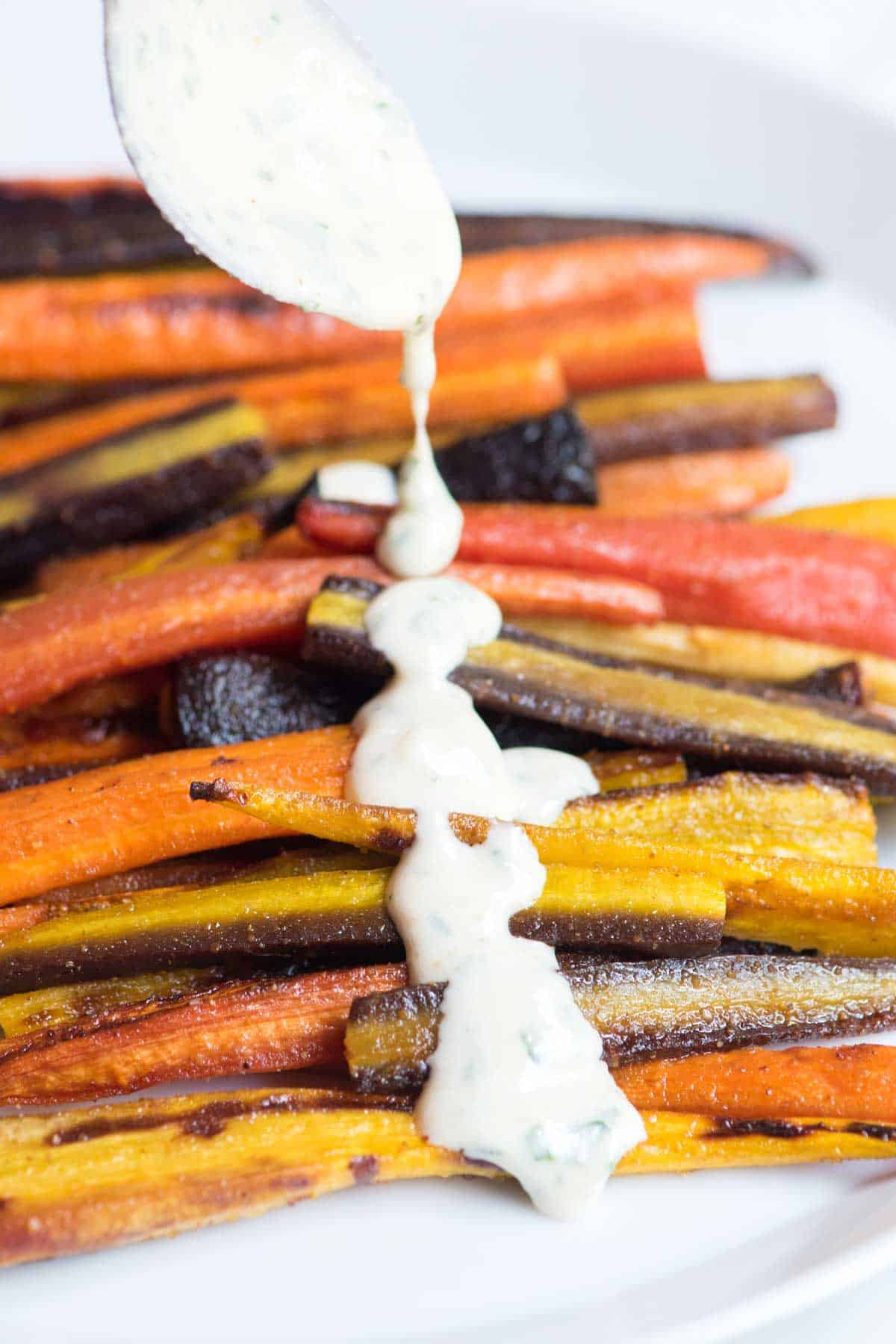Honey Roasted Carrots with tahini sauce being drizzled on top