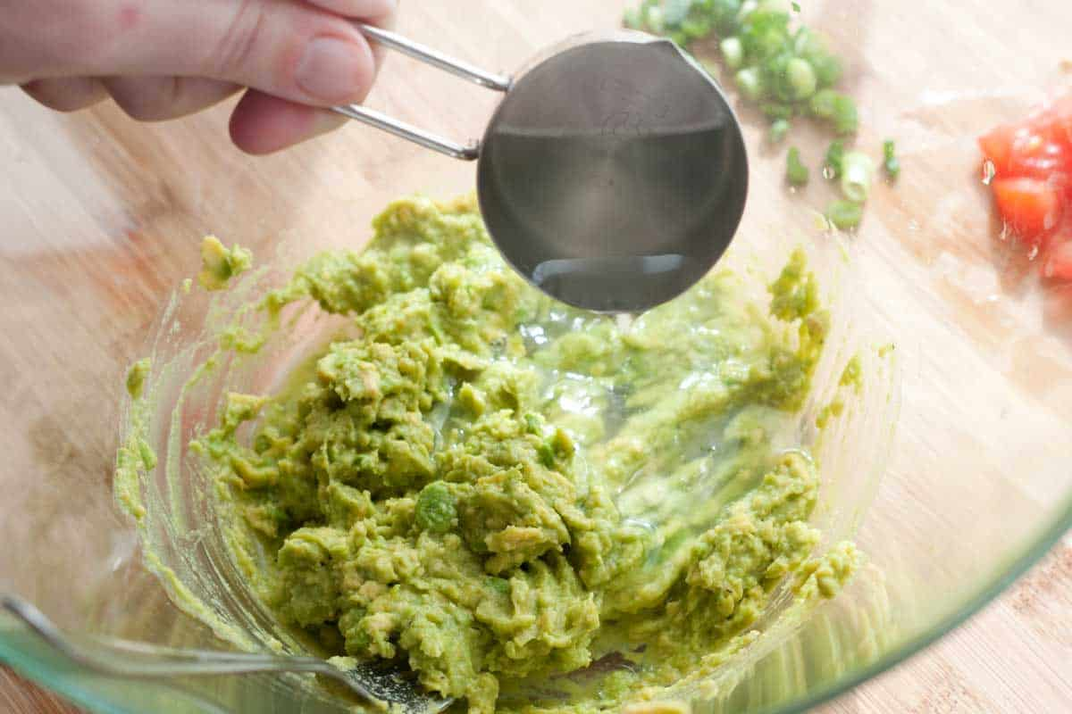 Adding a little hot pasta water to mashed avocado for the sauce