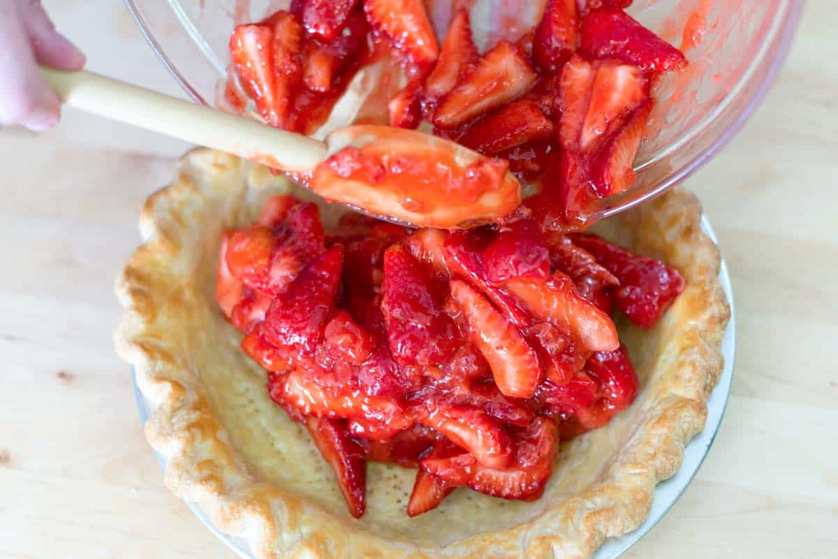 Adding the strawberry pie filling to the baked pie crust