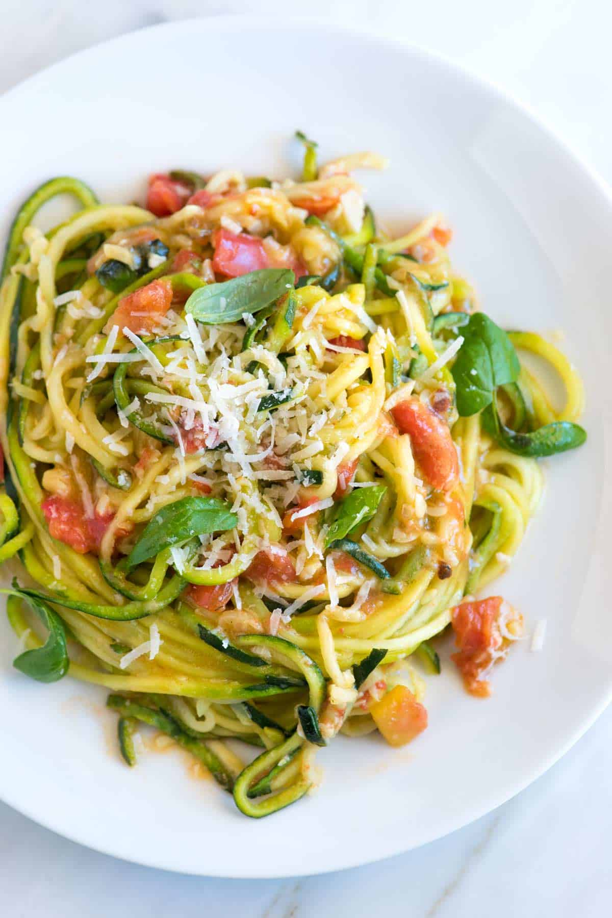 How to Make Guilt-Free, 20 Minute Garlic Parmesan Zucchini Pasta // My favorite way to cook zucchini noodles! See how to make our 20-minute zucchini noodles pasta recipe with garlic, tomatoes, basil, and parmesan cheese. Low-carb, keto-adaptable, and vegetarian!