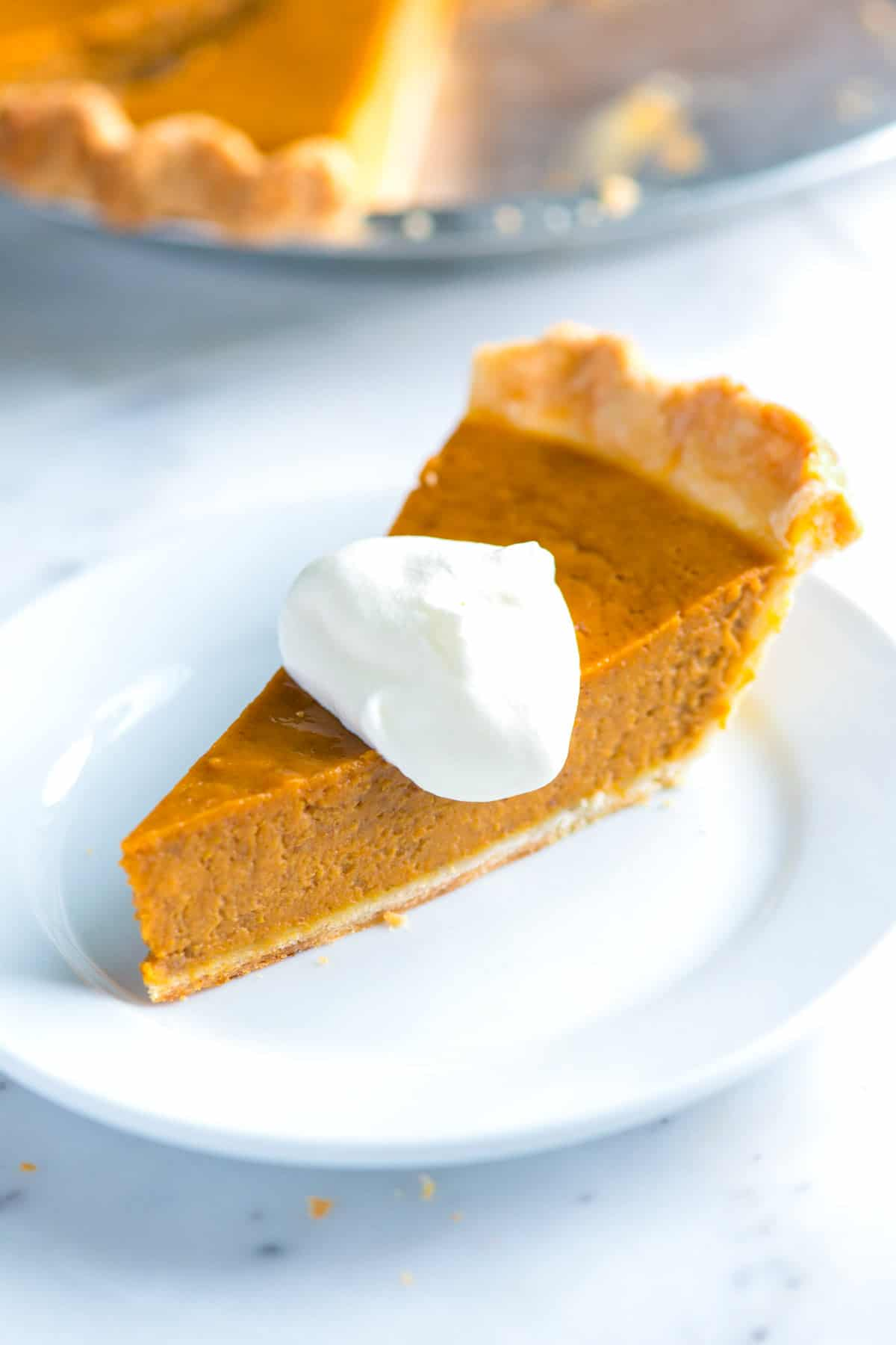 Easy, homemade pumpkin pie recipe with pumpkin puree (canned or homemade), eggs, cream, sugar and spices. Easy from scratch recipe with video!