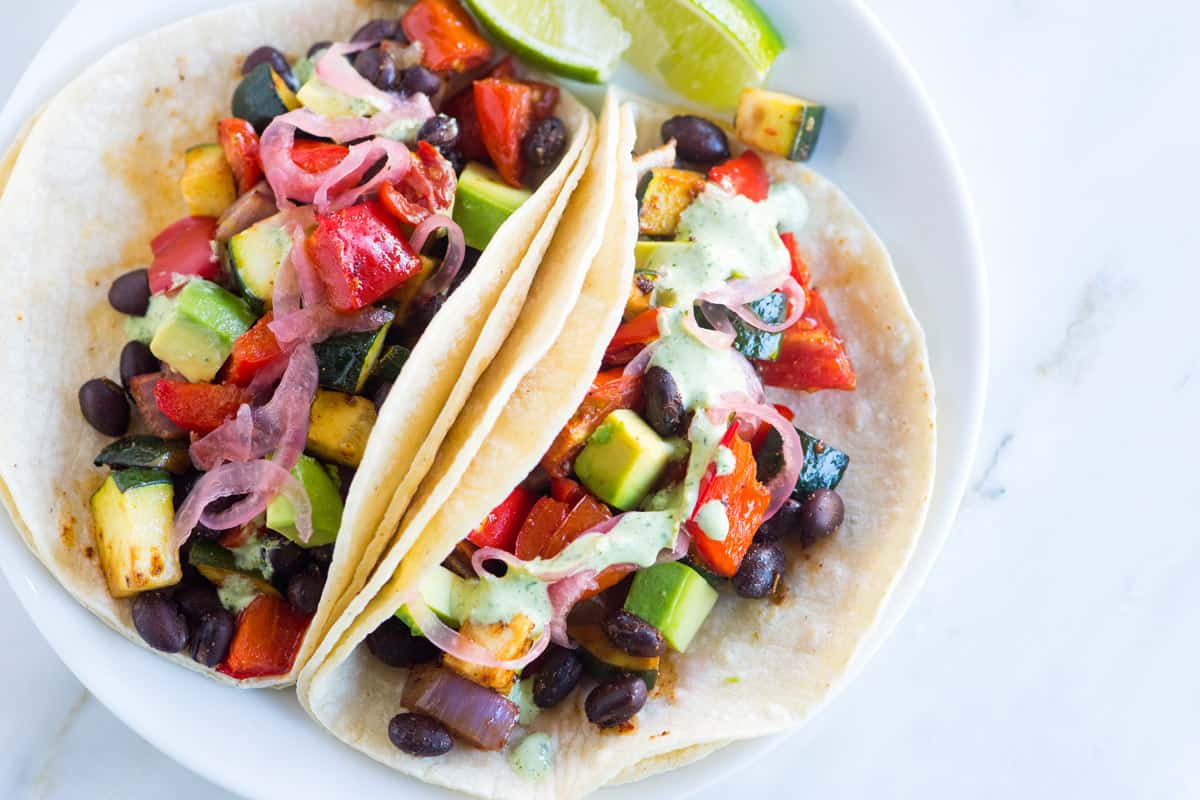 My favorite veggie tacos featuring flavorful roasted vegetables, hearty black beans, and a delicious five minute creamy cilantro sauce. These meatless tacos are simple to make and will satisfy the pickiest of eaters.