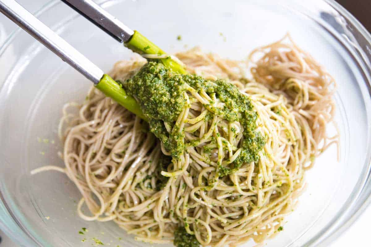 Tossing the pesto with soba noodles.