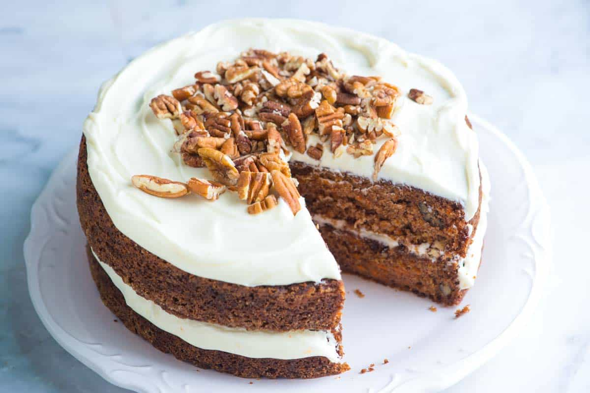 An 8-inch round carrot cake with a slice cut out