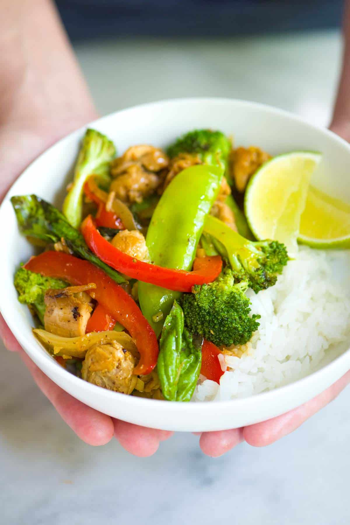 Bowl of chicken stir fry with vegetables and rice