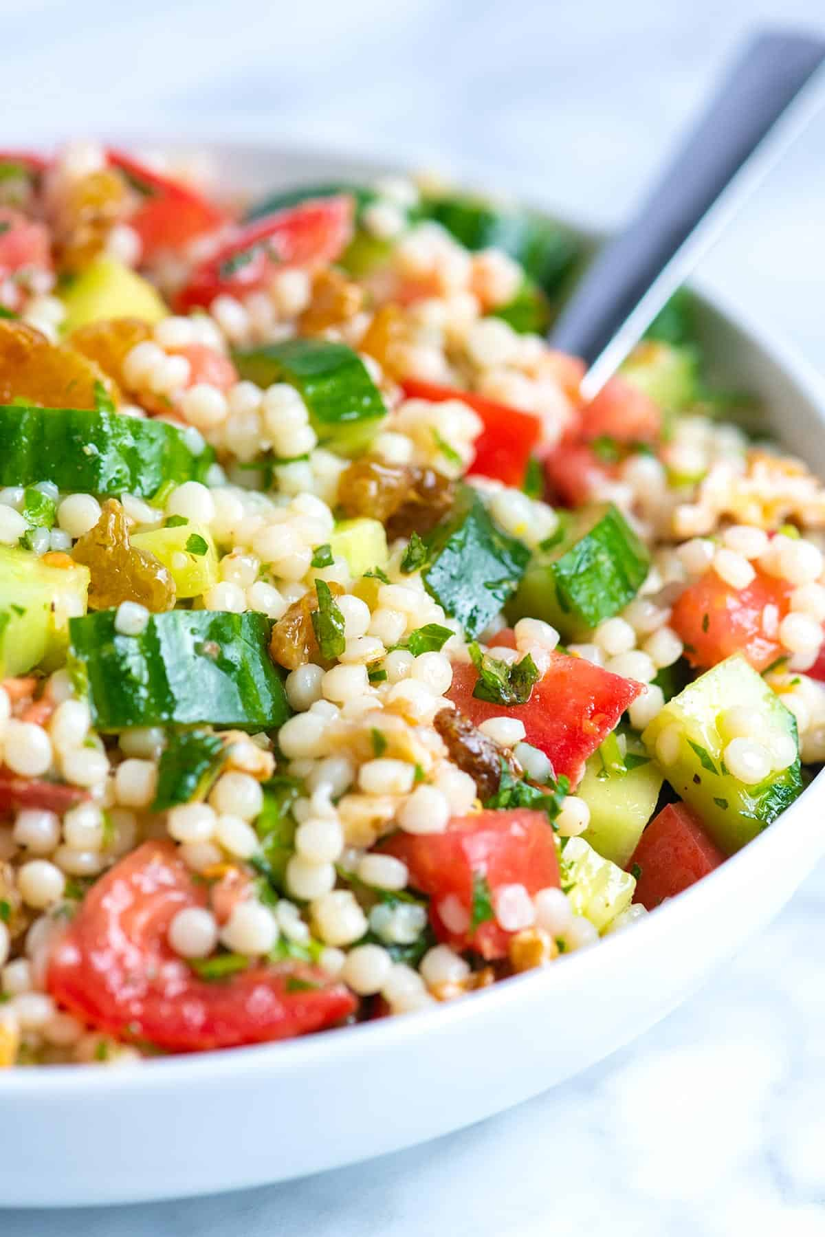 How to make the best couscous salad recipe with a simple lemon dressing, cucumber and lots of fresh herbs. See the easy recipe and video.