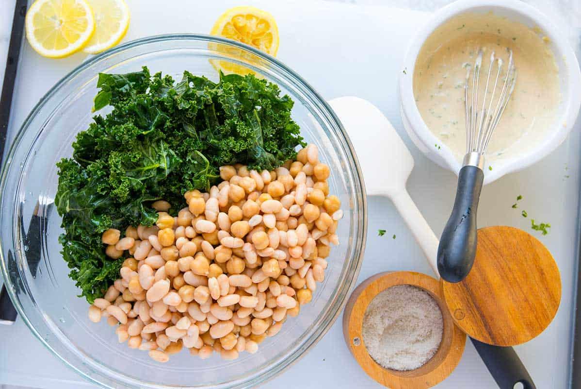 Making a bean salad recipe with kale, tahini and walnuts.