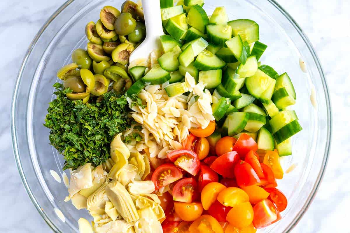Everyone loves this easy orzo pasta salad recipe with a simple lemon vinaigrette, cucumber, olives, tomato and fresh herbs.