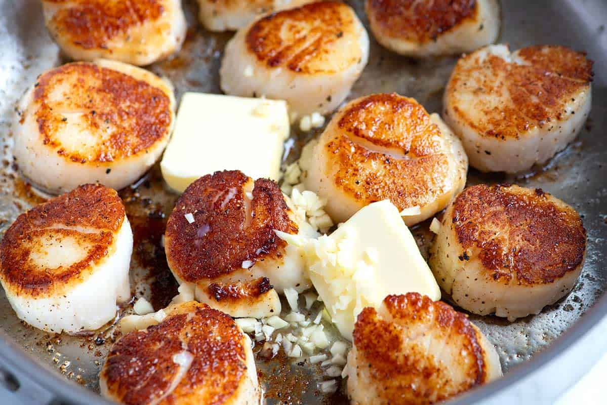 How to Cook Scallops like a Pro -- Adding a bit of creamy butter, garlic and fresh herbs at the end of cooking makes scallops that are restaurant worthy.