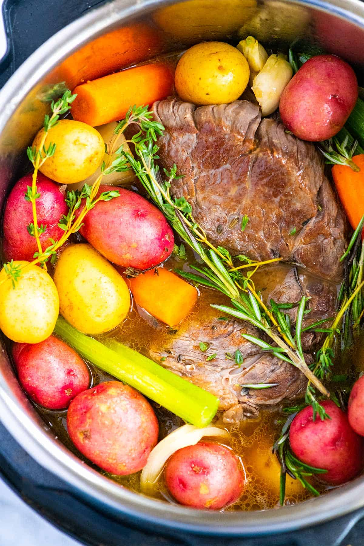 Instant Pot Pot Roast with potatoes, carrots, and herbs.