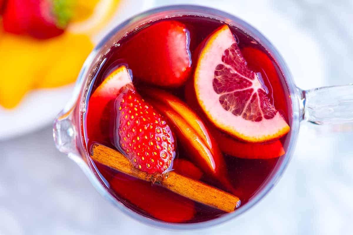 Nuestra receta favorita de sangría roja con vino tinto seco, frutas de temporada y brandy (opcional).