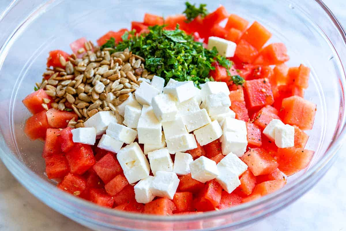 Watermelon Salad ingredients include watermelon, feta, fresh herbs, sunflower seeds, red wine vinegar, and olive oil.