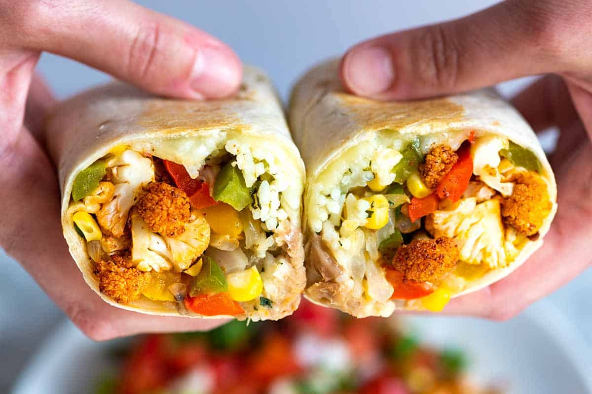 Quick and easy veggie burritos with spicy cauliflower, onions, peppers, rice, cheese, and beans. Easy to make and freezer friendly!