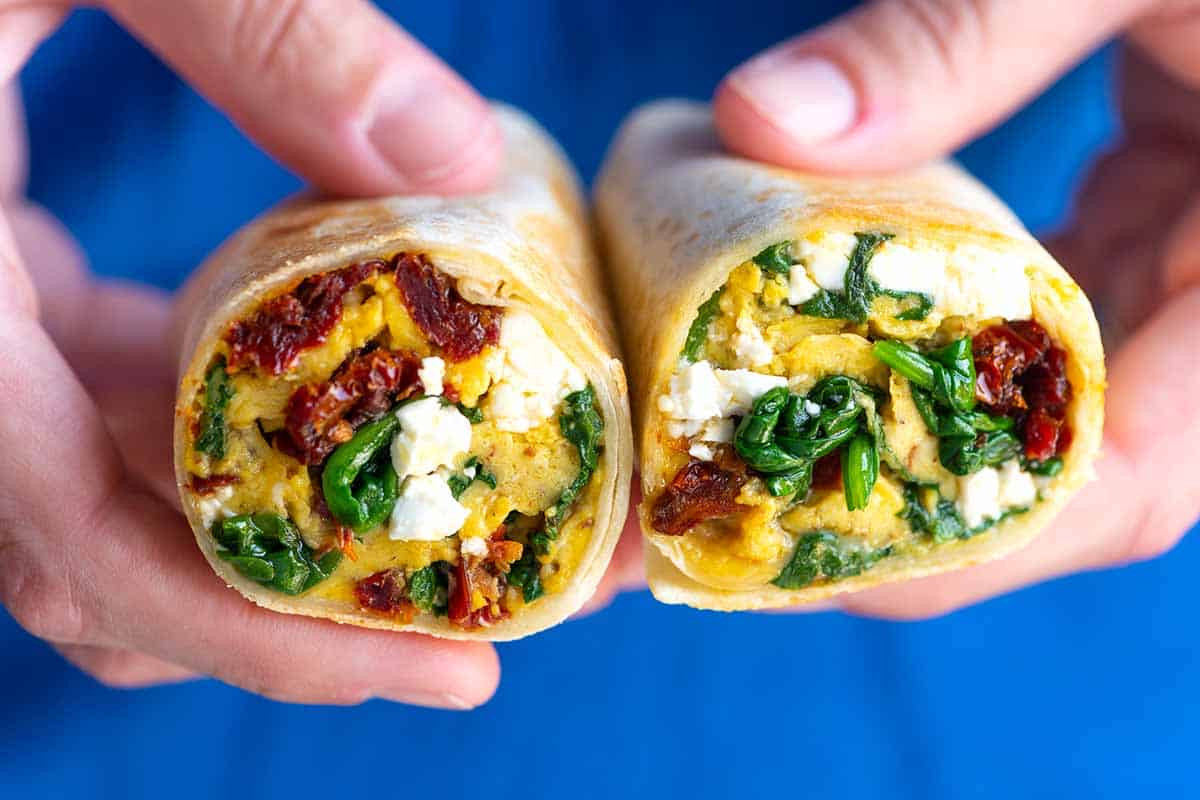 Packed with scrambled eggs, sun-dried tomatoes, spinach, and feta cheese, these healthier breakfast burritos are the perfect hand-held breakfast.