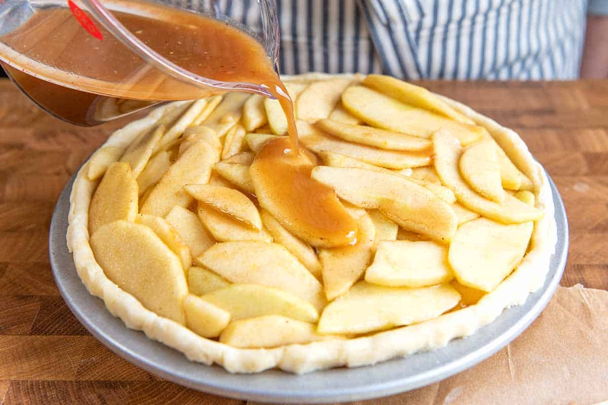 Adding apples and pie filling to the pie dish.