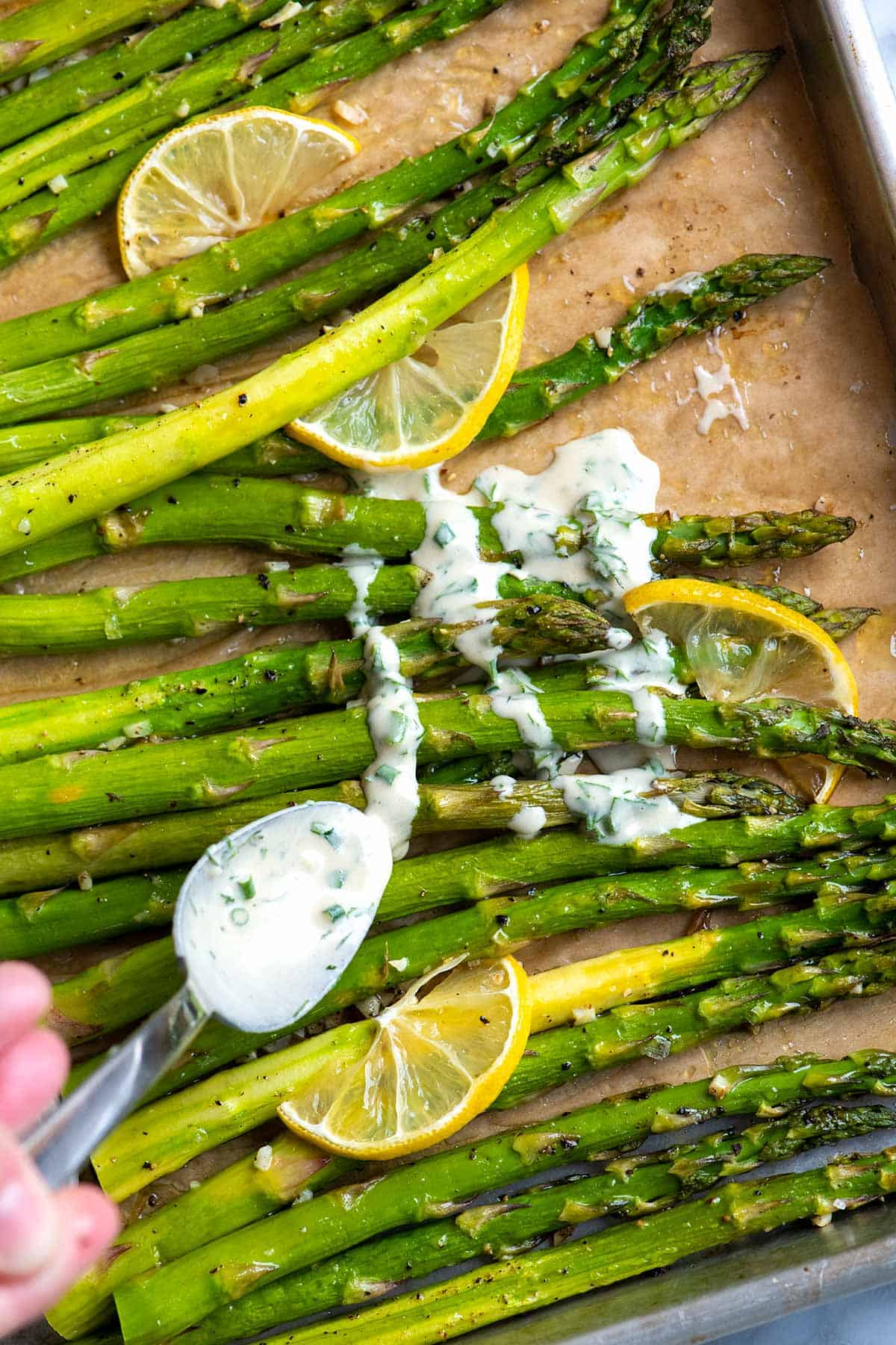 This roasted asparagus is a simple, fast side dish. The asparagus is perfectly tender with slightly crispy tips.  Served with our five minute garlic herb sauce, it's deliciously garlicky, fresh, and vegetarian.