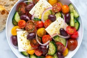 A bowl filled Greek salad made with a salad made of cucumbers, tomatoes, olives, red onion, and feta cheese.
