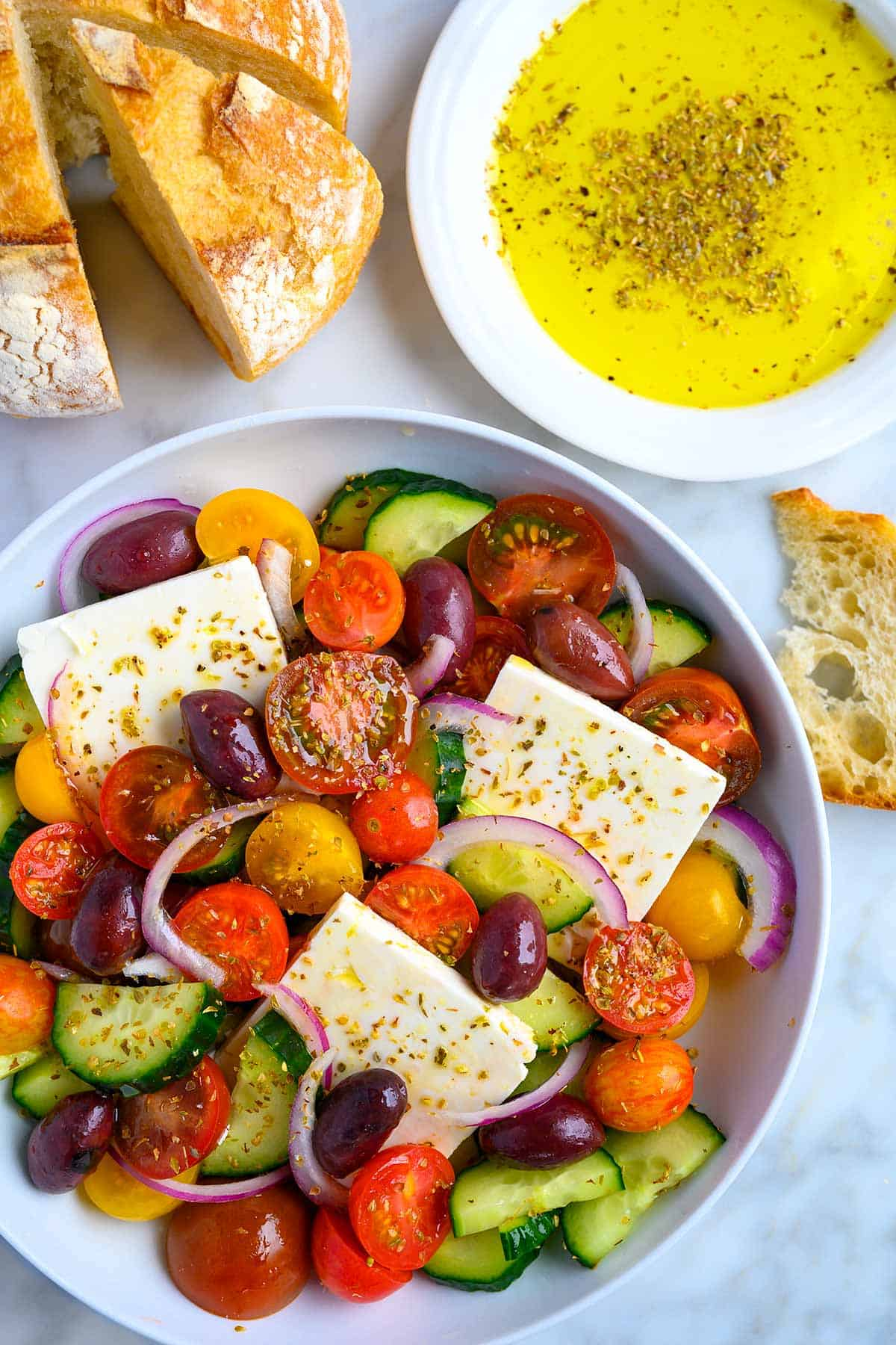 Bowl filled with a Greek salad with bread and dipping oil to the side.