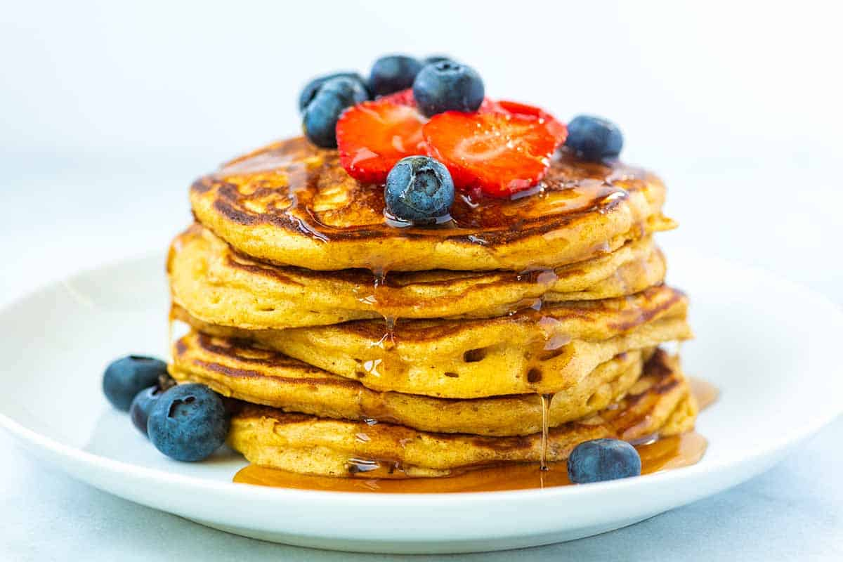 Stack of fluffy buttermilk pancakes with syrup and berries