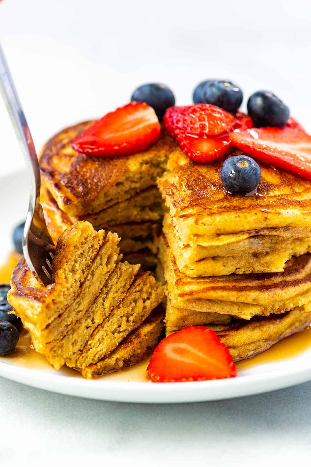 Stack of buttermilk pancakes with a fork, syrup and berries