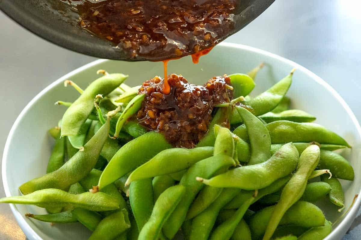Tossing garlic sauce with cooked edamame