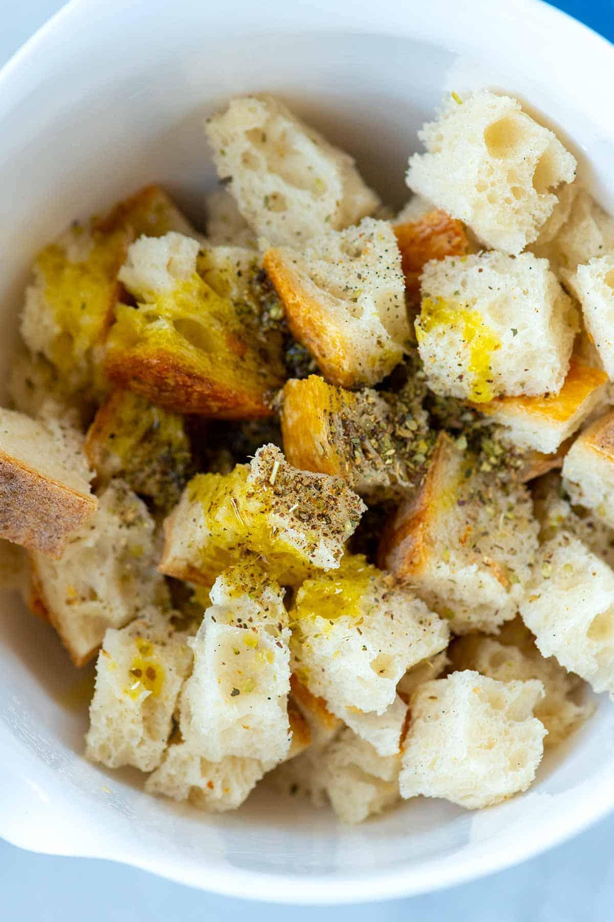 Pan en cubos mezclado con aceite de oliva, sal, pimienta y hierbas.