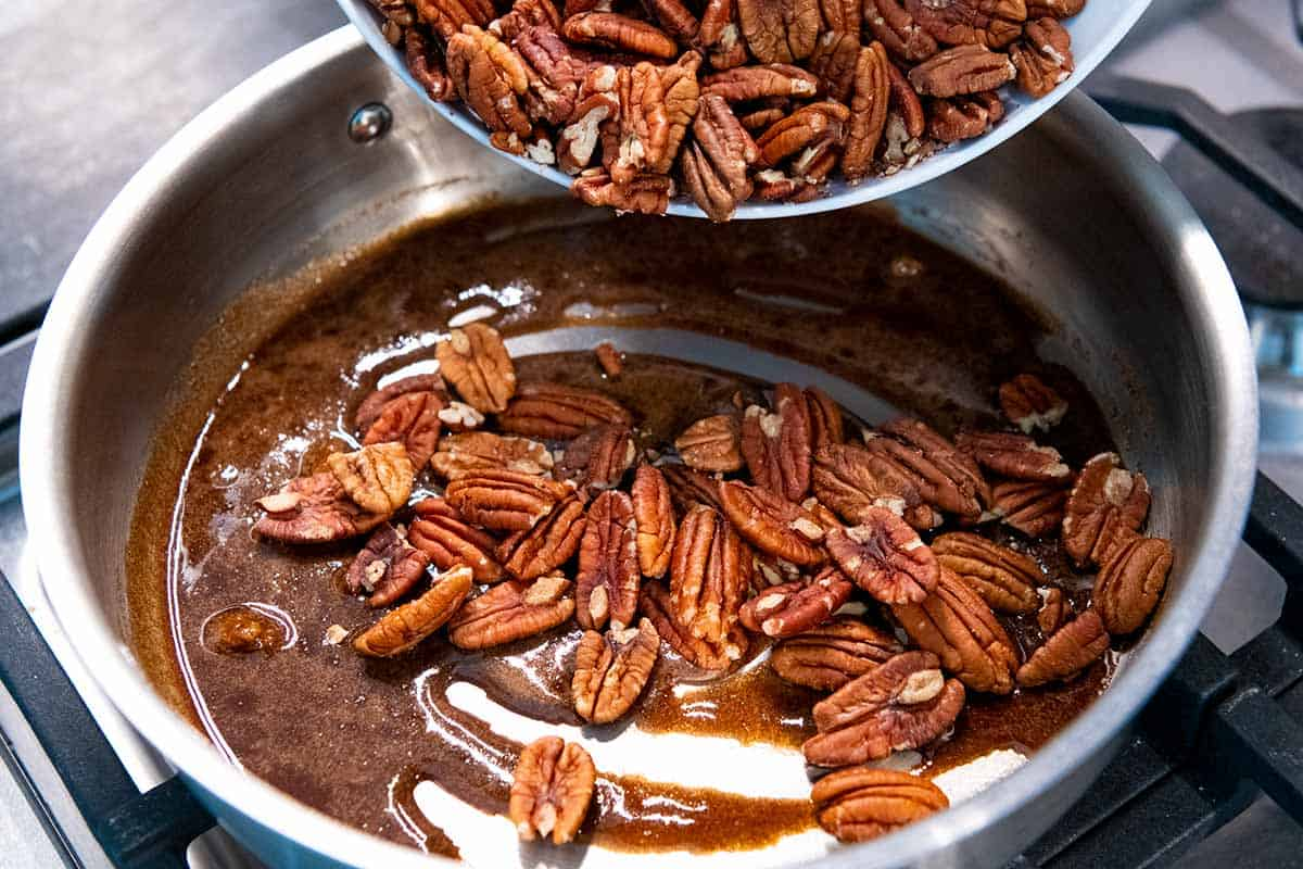 Adding pecans to brown sugar and spices for candied pecans.