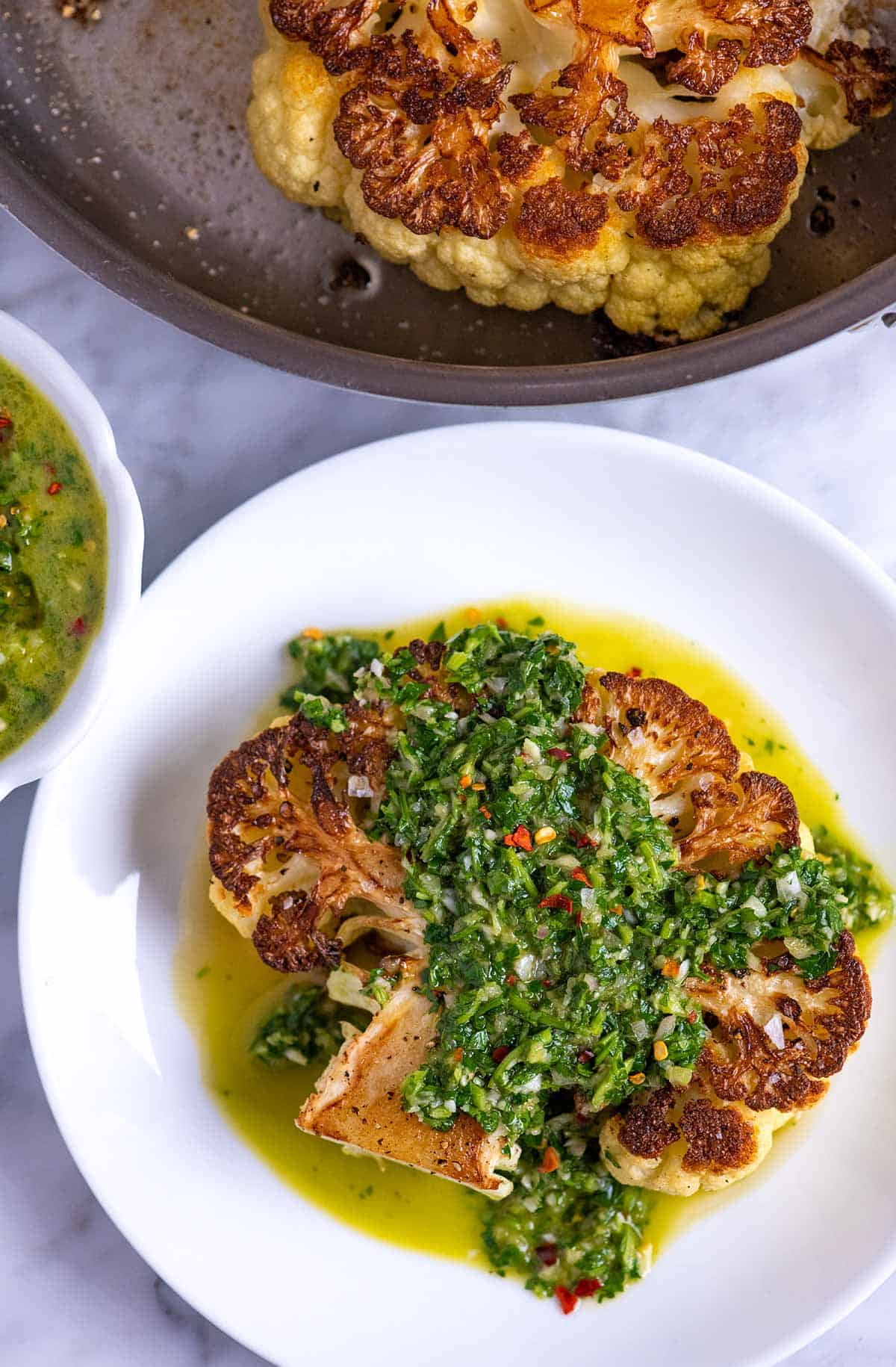 Roasted cauliflower steaks with chimichurri sauce spooned over the top
