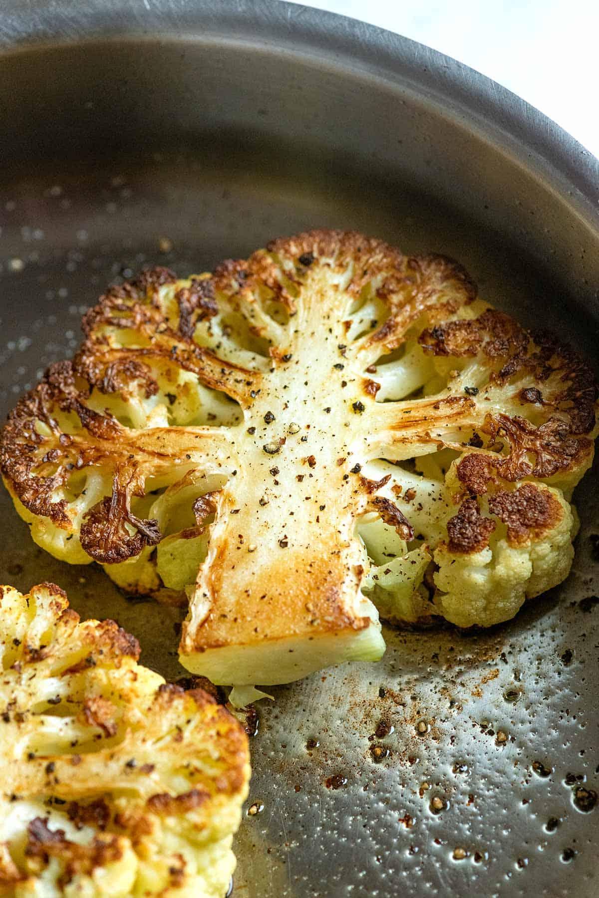 Schrittfoto, das zeigt, wie man Blumenkohlsteaks in einer Pfanne kocht.  Der Blumenkohl ist goldbraun und leicht mit Salz gewürzt.