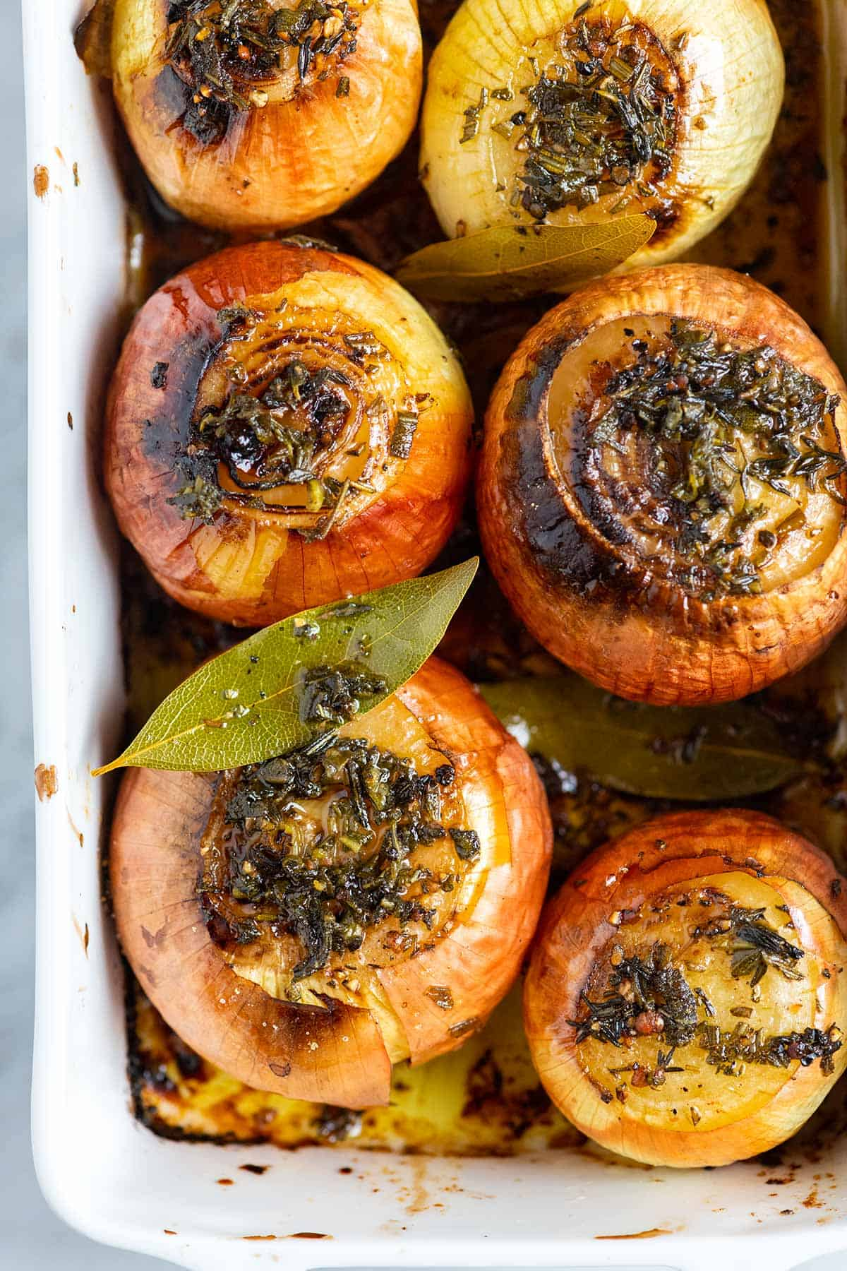 Whole roasted onions in a baking dish.