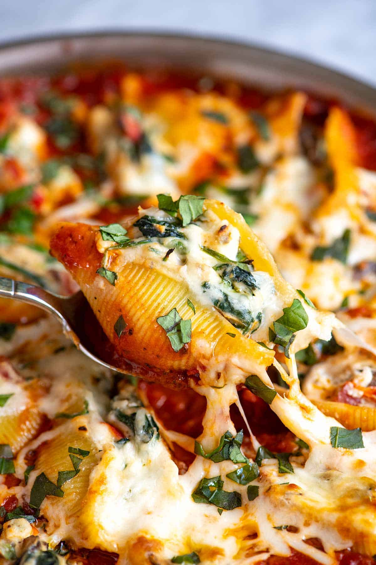 Pulling out one cheese and vegetable stuffed shell from the baking pan