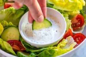 Dipping cucumber into homemade ranch dressing
