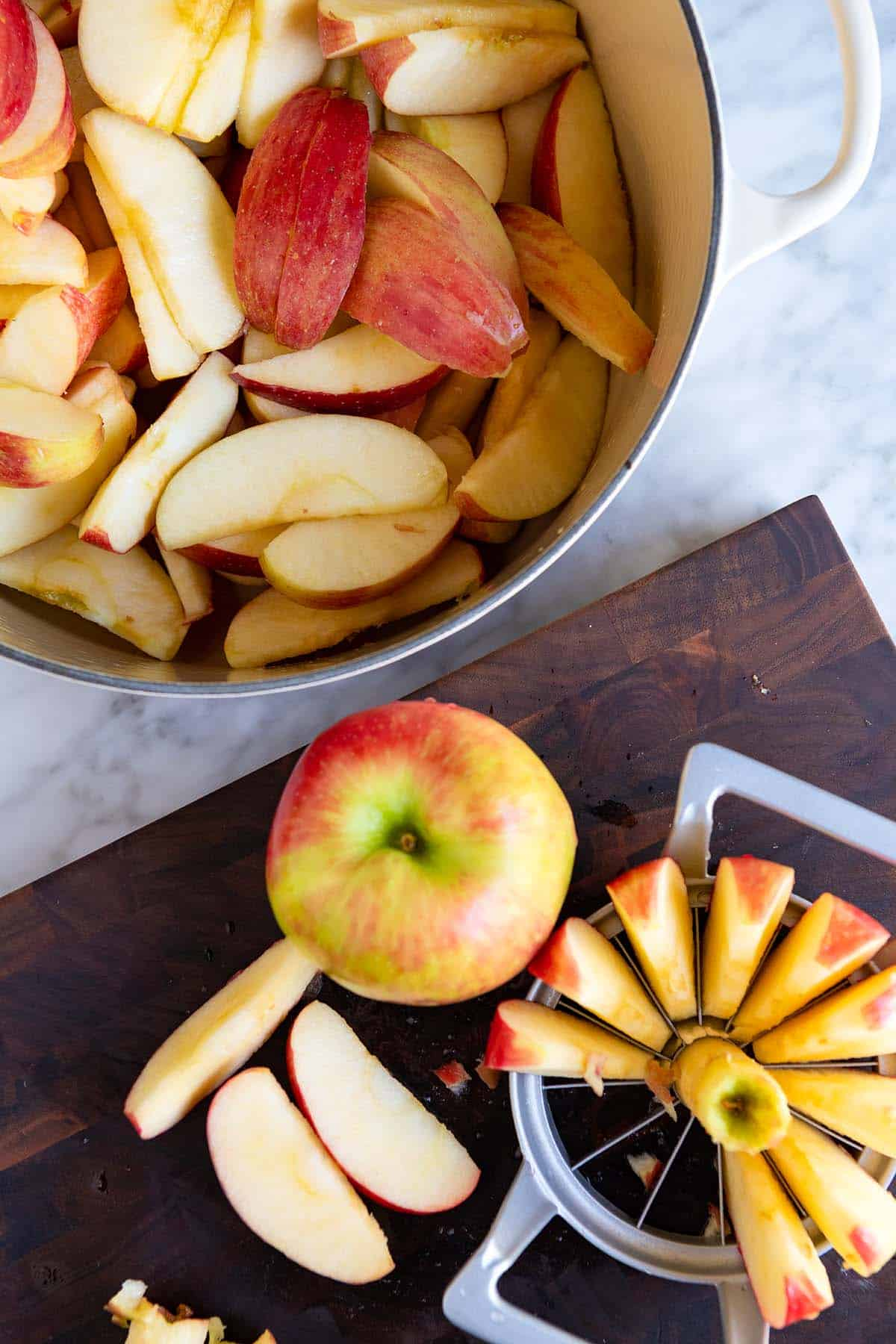 Step shot showing apples cut into wedges ready for making applesauce.